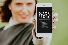 Black Friday banner in a mobile phone screen. Woman holding mobile phone with Black Friday banner in the screen Stock Photography