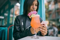 Woman Holding Mobile Phone with a Cocktail Glass on the Table stock photos