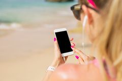 Free Woman Holding Mobile Phone In Hand And Listening To Music On Earbuds Stock Photography - 109536302