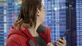 Woman holding mobile phone and looking at information board in airport. Woman traveller holding mobile phone and looking at information board in airport stock video footage