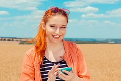 Woman holding mobile phone looking at you camnera smiling stock photos