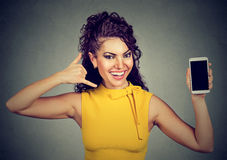 Woman holding mobile phone showing call me sign hand gesture Stock Image