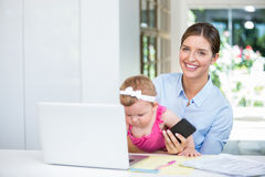 Woman holding mobile phone while sitting with baby girl Royalty Free Stock Images
