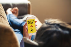 Woman holding a mobile phone with spyware alert notification in. Spyware alert notification in a mobile phone held by woman while lying on the sofa at home Stock Image