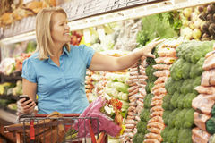 Woman Holding Mobile Phone In Supermarket Royalty Free Stock Images