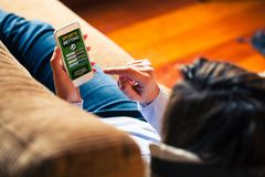 Sports betting app in a mobile phone screen. Woman holding a mobile phone to visit a sports betting website while lies down at home stock photos