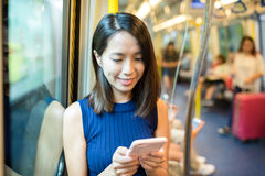Woman holding a mobile phone. In train compartment Royalty Free Stock Image