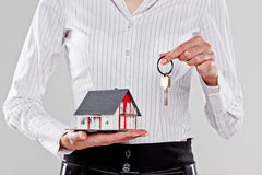 Woman holding a model of a detached house and the keys Stock Photography