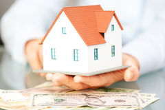 Woman holding a model house on top of a pile of dollars Stock Photos