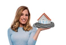 Woman holding model of a house warmed by a scarf. Isolated on white. stock photo