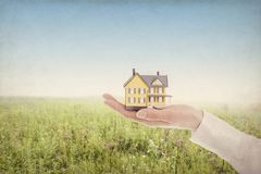 Woman holding model toy house in palm of hands abasing a blue sky. Woman holding model toy house in palm of hands against a blue sky with tone and texture Royalty Free Stock Photos