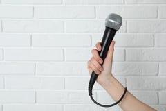 Woman holding modern microphone near wall, closeup. Space for text. Woman holding modern microphone near brick wall, closeup. Space for text royalty free stock image