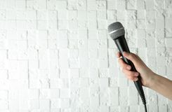 Woman holding modern microphone near white wall, closeup. Space for text royalty free stock photography