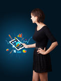 Woman holding modern tablet with colorful diagrams and graphs Stock Photos