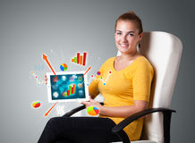 Woman holding modern tablet with colorful diagrams and graphs Stock Photo
