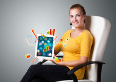 Woman holding modern tablet with colorful diagrams and graphs Stock Images