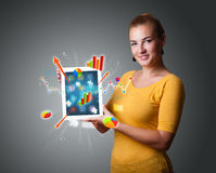 Woman holding modern tablet with colorful diagrams and graphs Stock Photography
