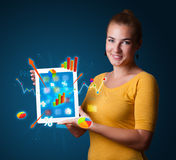 Woman holding modern tablet with colorful diagrams and graphs Royalty Free Stock Photo