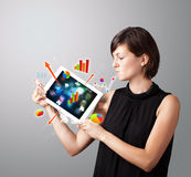 Woman holding modern tablet with colorful diagrams and graphs Stock Image