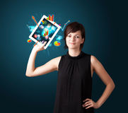 Woman holding modern tablet with colorful diagrams and graphs Royalty Free Stock Images