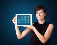 Woman holding modern tablet with colorful icons Royalty Free Stock Image