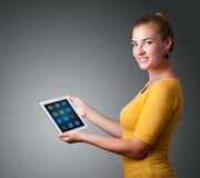 Woman holding modern tablet with colorful icons Stock Photos