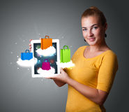 Woman holding modern tablet with colorful shopping bags on cloud Stock Photos
