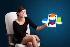 Woman holding modern tablet with colorful shopping bags on cloud Stock Image