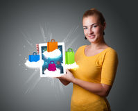 Woman holding modern tablet with colorful shopping bags on cloud Stock Photo