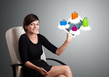 Woman holding modern tablet with colorful shopping bags on cloud Stock Images