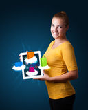 Woman holding modern tablet with colorful shopping bags on cloud. Beautiful woman holding modern tablet with colorful shopping bags on clouds Stock Images