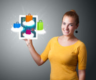 Woman holding modern tablet with colorful shopping bags on cloud Royalty Free Stock Images