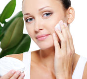 Woman holding moisturizer and applying it on face Royalty Free Stock Photo