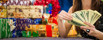 Woman holding monay at holiday gifts background Royalty Free Stock Photography