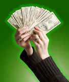 Woman holding money. Womans hands holding fanned out money, with green glowing background