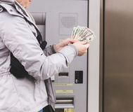 Woman Holding Money at Automated Teller Machine Stock Photos