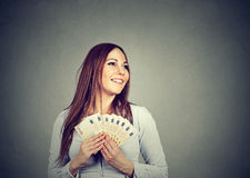 Woman holding money euro banknotes dreaming how to spend Stock Photo