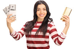 Woman holding money and a gold bar. Studio shot of a joyful woman holding a few stacks of money and a gold bar isolated on white background royalty free stock photos