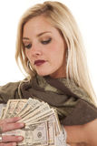 Woman holding money by heart looking at it Royalty Free Stock Photo