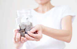 A Woman holding money jar with coins close up Royalty Free Stock Images