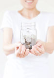 A Woman holding money jar with coins close up Royalty Free Stock Image