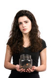 Woman Holding Money Jar. Young woman holds a jar of money with a questioning look on her face to portray a inadequate savings concept Royalty Free Stock Photos