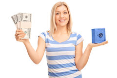 Woman holding money and a small safe Stock Photo