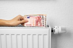 Woman holding money. On heating battery background Royalty Free Stock Photo
