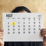 Woman holding Monthly calendar of May. 6th May 2019 marked as Ramadan beginning day royalty free stock image