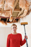 Woman Holding Mop Under Damaged Ceiling Stock Photo