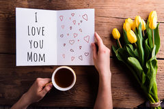 Woman holding Mothers day greeting and coffee. Yellow tulips. Royalty Free Stock Image