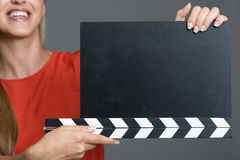 Woman with movie clapboard. A smiling woman holding a blank movie clapboard on a gray background Stock Photos