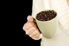 Woman holding mug of coffee beans Stock Photos