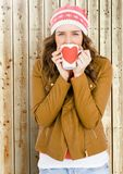 Woman holding a mug with a heart shape on it. Portrait of woman holding a mug with a heart shape on it in front of wooden background Stock Images